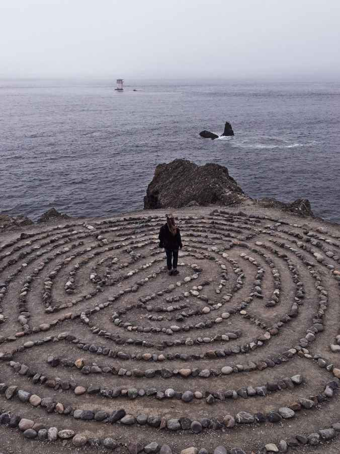 unrecognizable woman in center of stony labyrinth on seashore